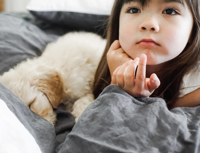 Girl and Dog on French Linen Bedding